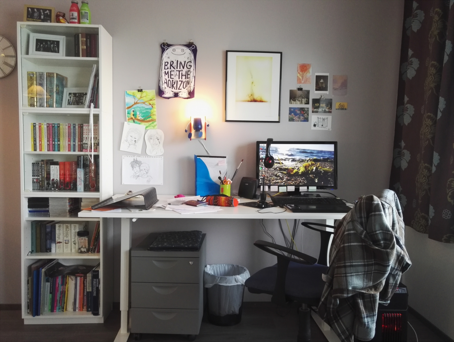 A photo of my working space. My desk in the centre, a narrow bookshelf to the left, postcards and other art on the wall.